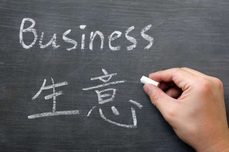 Business- word written on a smudged blackboard with a Chinese translation,with a hand holding chalk Standard-Bild