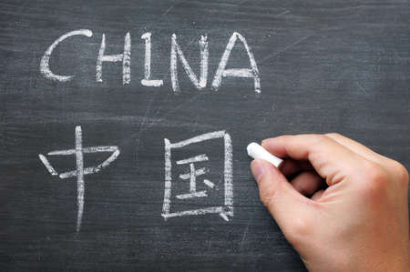 China - word written on a smudged blackboard with a Chinese version, with a hand holding chalk photo