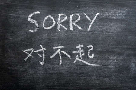Sorry - word written on a smudged blackboard with a Chinese translation photo