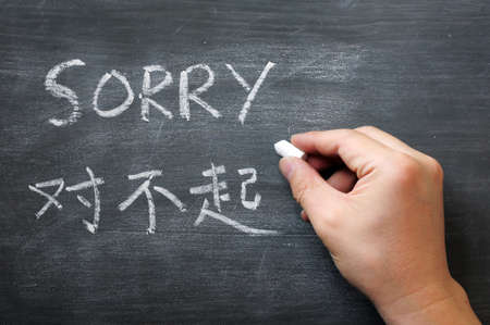 Sorry - word written on a smudged blackboard with a Chinese translation, with a hand holding chalk Stock Photo