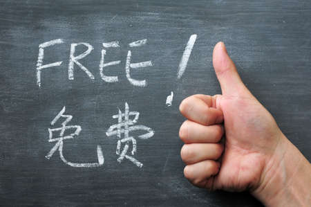 Free - word written on a smudged blackboard with a Chinese translation, with a thumb up gesture photo