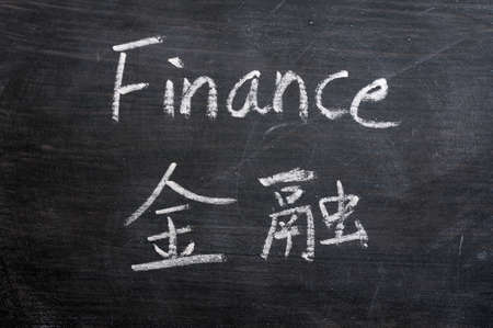 Finance - word written on a smudged blackboard with a Chinese translation photo