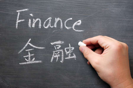 Finance - word written on a smudged blackboard with a Chinese translation,with a hand holding chalk photo