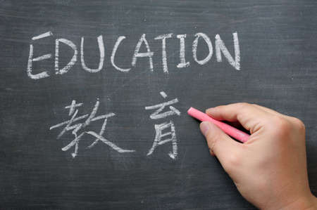 Education - word written on a smudged blackboard with a Chinese translation,with a hand holding chalk