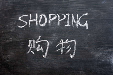 Shopping - word written on a smudged blackboard with a Chinese translation photo
