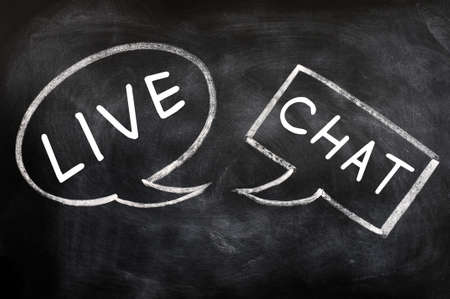 Two speech bubbles for live chat drawn with chalk on a blackboard photo