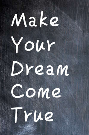 realize: Make Your Dream Come True - written with white chalk on a smudged blackboard background