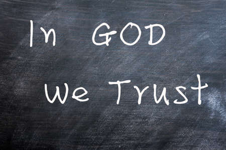 in god we trust: In God we trust - written with chalk on a smudged blackboard background Stock Photo