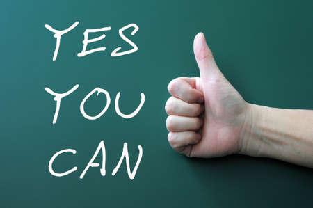 you can: Sí se puede - escrito con tiza en una pizarra de fondo, con los pulgares arriba gesto Foto de archivo