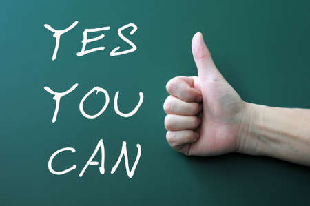 Yes you can - written with chalk on a blackboard background,with thumbs up gesture photo