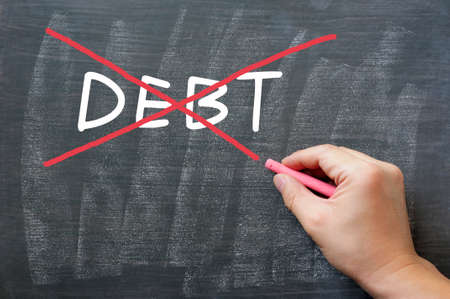 Debt written on a smudged blackboard, being crossed out photo