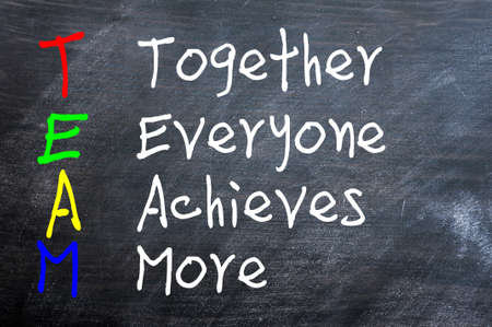 achieves: TEAM acronym for Together Everyone Achieves More written on a smudged blackboard Stock Photo