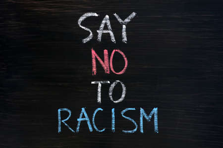 racism: Say no to racism written on a smudged blackboard background