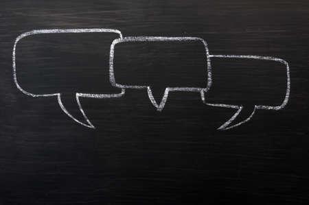 chat balloon: Three speech bubbles drawn with chalk on a blackboard Stock Photo