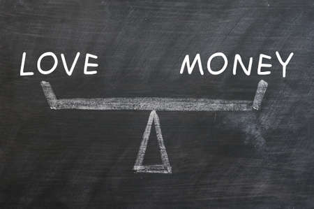 Balance of love and money drawn with chalk on a blackboard photo