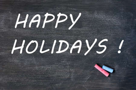 Happy holidays written on a smudged blackboard with chalk Stock Photo - 14062861