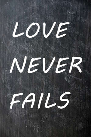 fails: Love Never Fails written on a smudged chalkboard Stock Photo