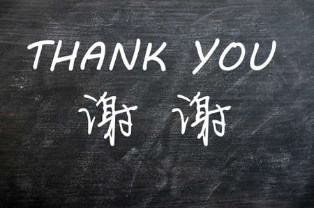 Thank you written in English and Chinese on a blackboard photo