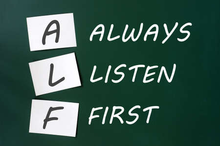 listen fist: ALF acronym for Always Listen First on a green board Stock Photo