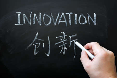 innovating: Innovation - word written with white chalk in both English and Chinese,with a hand holding chalk writing.