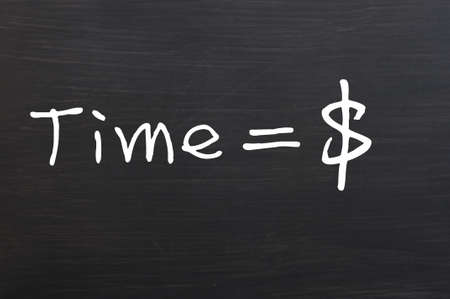 sign equals: Time is money, handwritten with white chalk on a blackboard Stock Photo