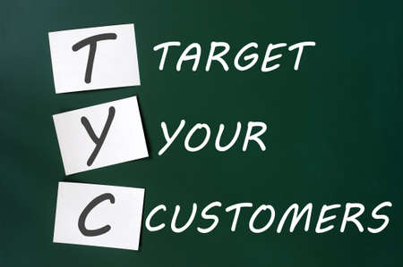 Target your customers concept written with white chalk on a blackboard photo