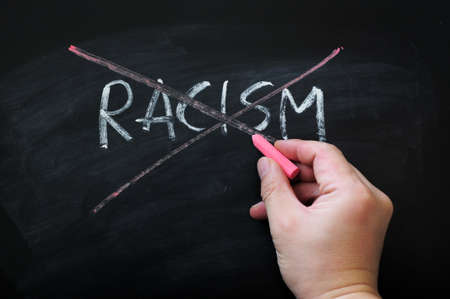 racism: Cross out racism on a smudged blackboard background with red chalk holding in hand