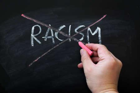 racismo: Tache el racismo en un fondo pizarra manchada de tiza roja sosteniendo en la mano