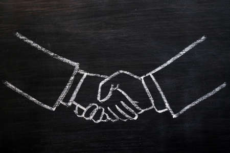 Chalk drawing of handshaking on a smudged blackboard
