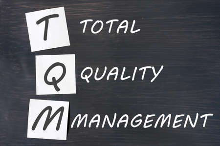Acronym of TQM for total quality management - white chalk handwriting and sticky notes on a blackboard  photo