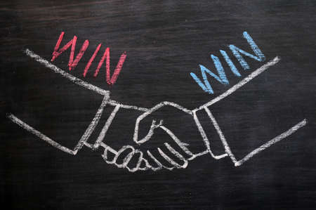 Mutual benefit or win-win concept of handshaking drawn with chalk on a blackboard Standard-Bild