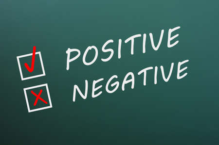 Chalk drawing of Positive and negative with check boxes on a green chalkboard photo