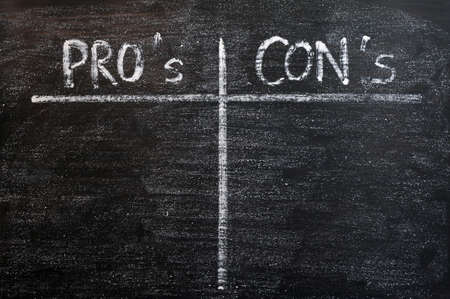 cons: Pros and cons list drawn with chalk on a blackboard, for and against argument