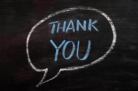 merci: Remerciez-vous �crit dans une bulle avec de la craie bleue sur un tableau noir tach� Banque d'images