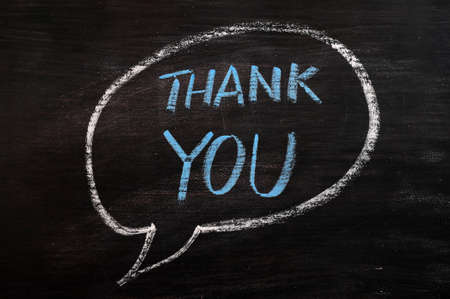 Thank you written in a speech bubble with blue chalk on a smudged blackboard photo