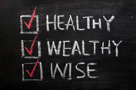 Being healthy, wealthy and wise with check boxes written in chalk on a blackboard