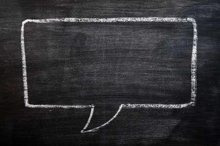 dialogo: Burbuja de di�logo en blanco dibujado con tiza sobre un fondo borroso pizarra para escribir el texto y el dise�o Foto de archivo