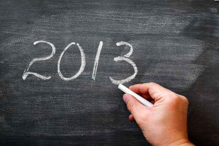 2013 written in chalk on a smudged blackboard,with a hand holding chalk photo