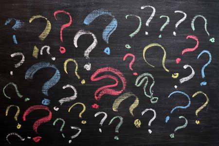 punto di domanda: Punti interrogativi sulla lavagna. La decisione, confusione, FAQ o altro concetto. Scrittura a mano con il gesso sulla consiglio scolastico nero.