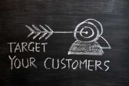 'Target your customers' concept drawn with white chalk on a blackboard Standard-Bild