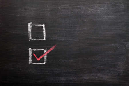 Check boxes with a red tick written with chalk on a smudged blackboard