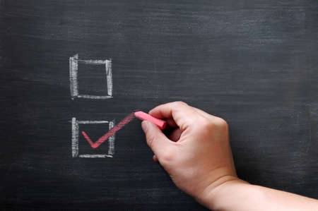 tick mark: Check boxes with a hand writing a tick with chalk on a smudged blackboard