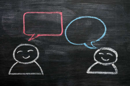 Blank speech bubbles with cartoon figures drawn on a blackboard background photo
