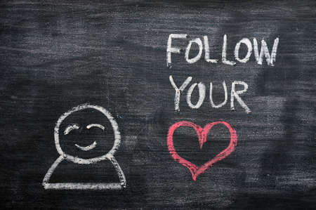 Speech bubble with a cartoon figure and the phrase Follow your heart drawn on a blackboard background photo
