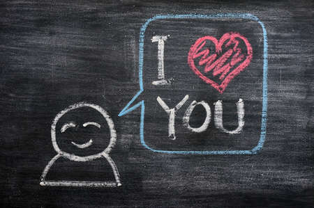 thinking of you: Speech bubble with a cartoon figure, saying I love you drawn on a blackboard background