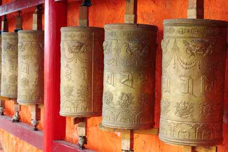 Row of golden Tibetan prayer wheels in a lamasery Stock Photo - 14309811