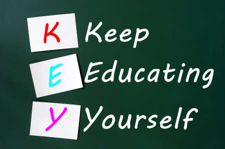KEY acronym -Keep educating yourself on a green chalkboard with sticky notes photo
