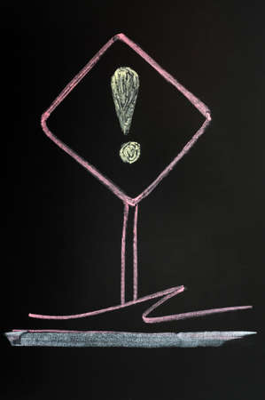 Exclamation mark warning sign drawn with red chalk on a blackboard background photo