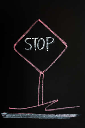 Stop warning sign drawn with red chalk on a blackboard background photo