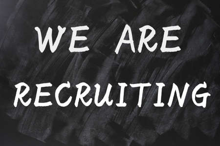 recruiting: Concept of we are recruiting written on a smudged blackboard background Stock Photo